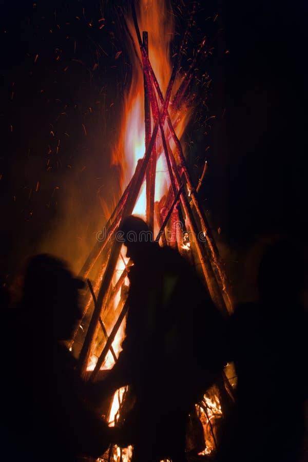 Fuego enorme en la noche y la gente joven alrededor fotos de archivo