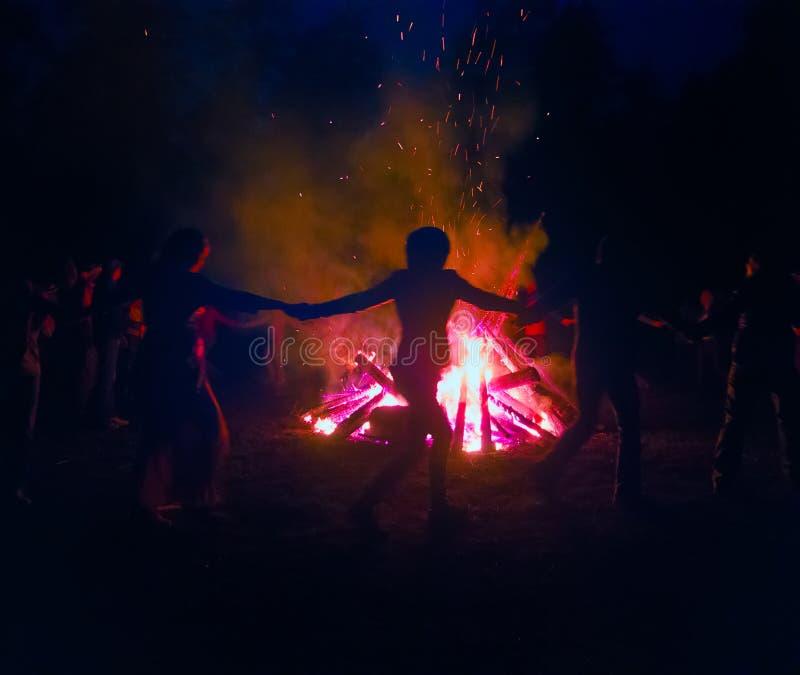 Fuego enorme en la noche y la gente joven alrededor imagen de archivo