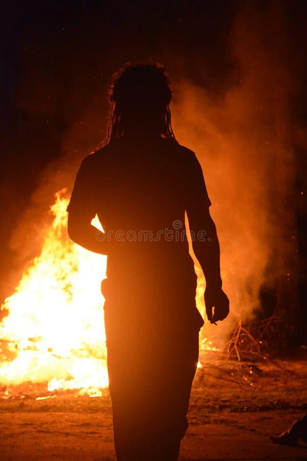 Fuego grande con la silueta masculina fotos de archivo