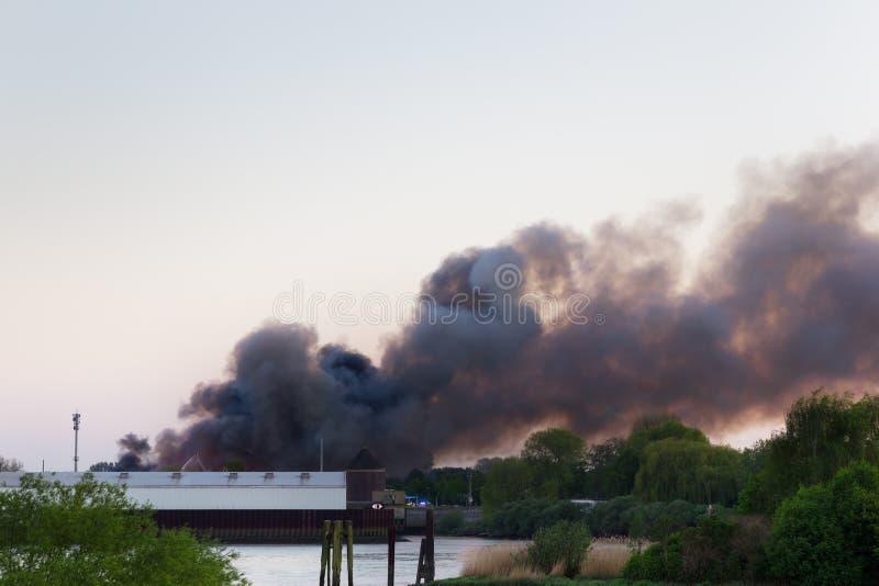 Fuego importante con humo oscuro foto de archivo
