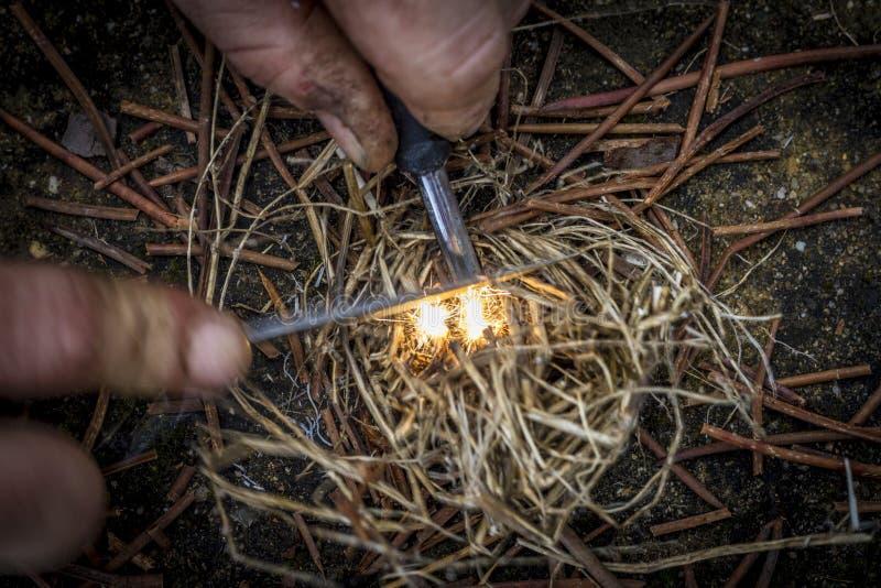 Fuego ligero con la yesca con sus manos fotografía de archivo