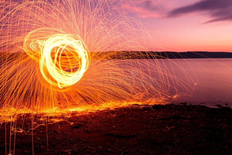 Fuego Poi en la puesta del sol en el lago fotos de archivo