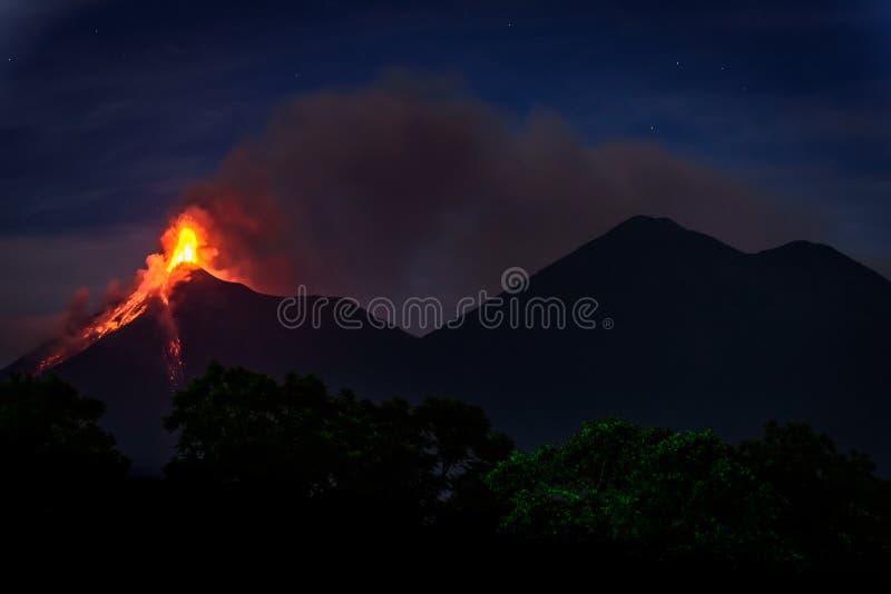 Fuego volcano erupting in Guatemala just before dawn. Lava & smoke spurt from erupting Fuego volcano next to Acatenango volcano at dawn near Antigua, Guatemala royalty free stock photos