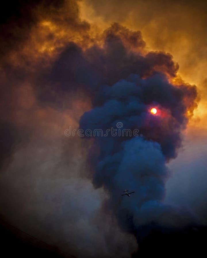 Fuego y humo en puesta del sol fotos de archivo