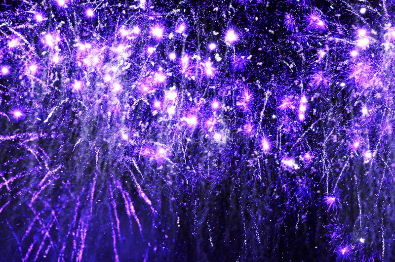 Fuegos artificiales chispeantes púrpuras que estallan en cielo nocturno negro fotografía de archivo