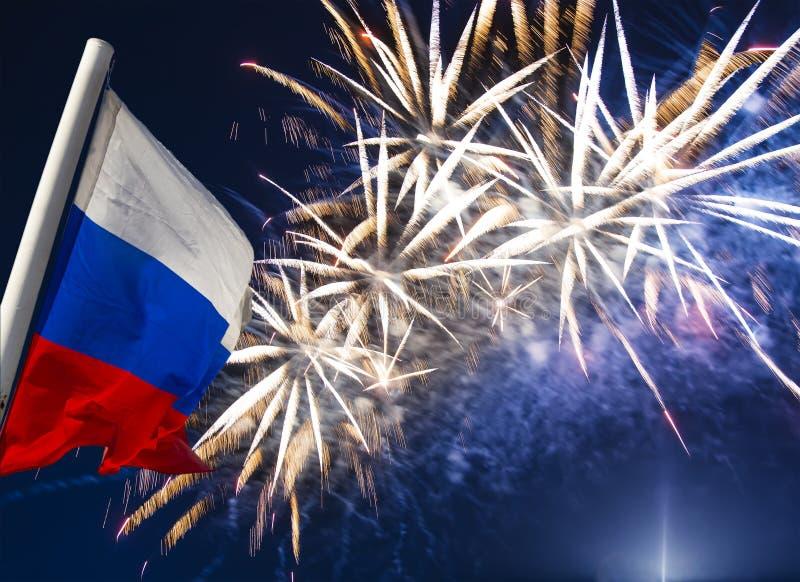 Fuegos artificiales coloridos celebradores que estallan en los cielos y la bandera de Rusia que agitan en el viento contra el cie fotos de archivo libres de regalías