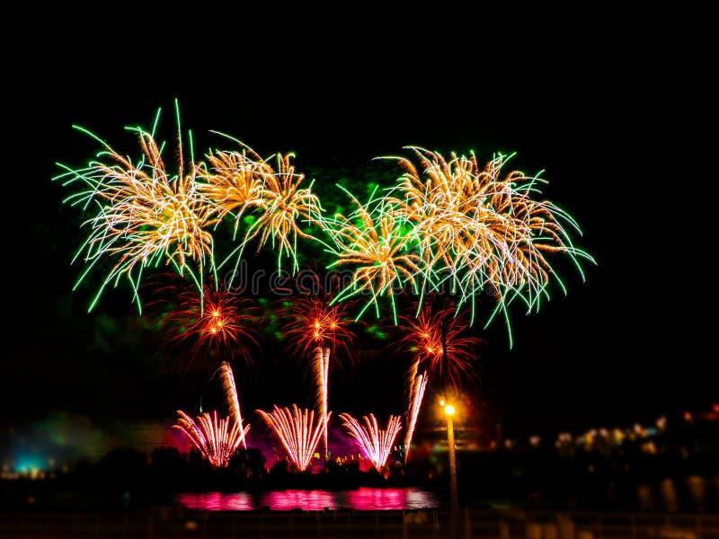Fuegos artificiales coloridos con explosiones múltiples contra el cielo oscuro imagenes de archivo