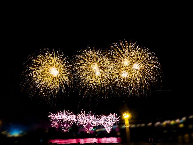 Fuegos artificiales coloridos con explosiones múltiples contra el cielo oscuro foto de archivo libre de regalías