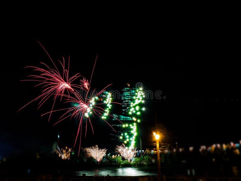 Fuegos artificiales coloridos con explosiones múltiples contra el cielo oscuro imagen de archivo