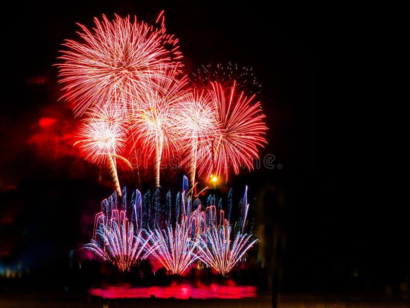 Fuegos artificiales coloridos con explosiones múltiples contra el cielo oscuro foto de archivo