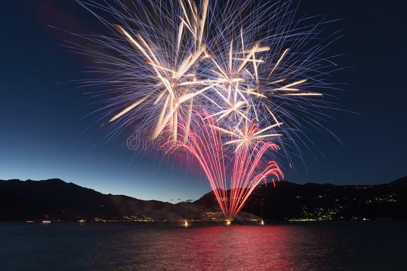 Fuegos artificiales en el lago en una noche de verano foto de archivo