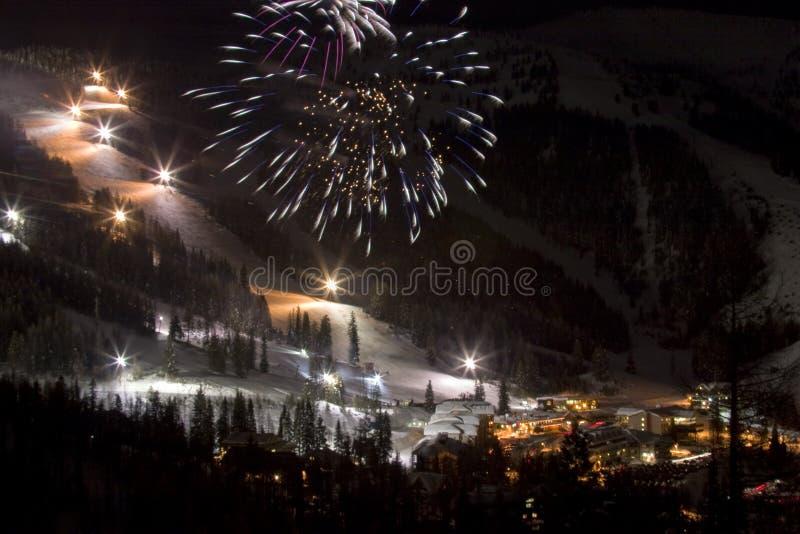 Fuegos artificiales en la noche en una cuesta del esquí foto de archivo libre de regalías