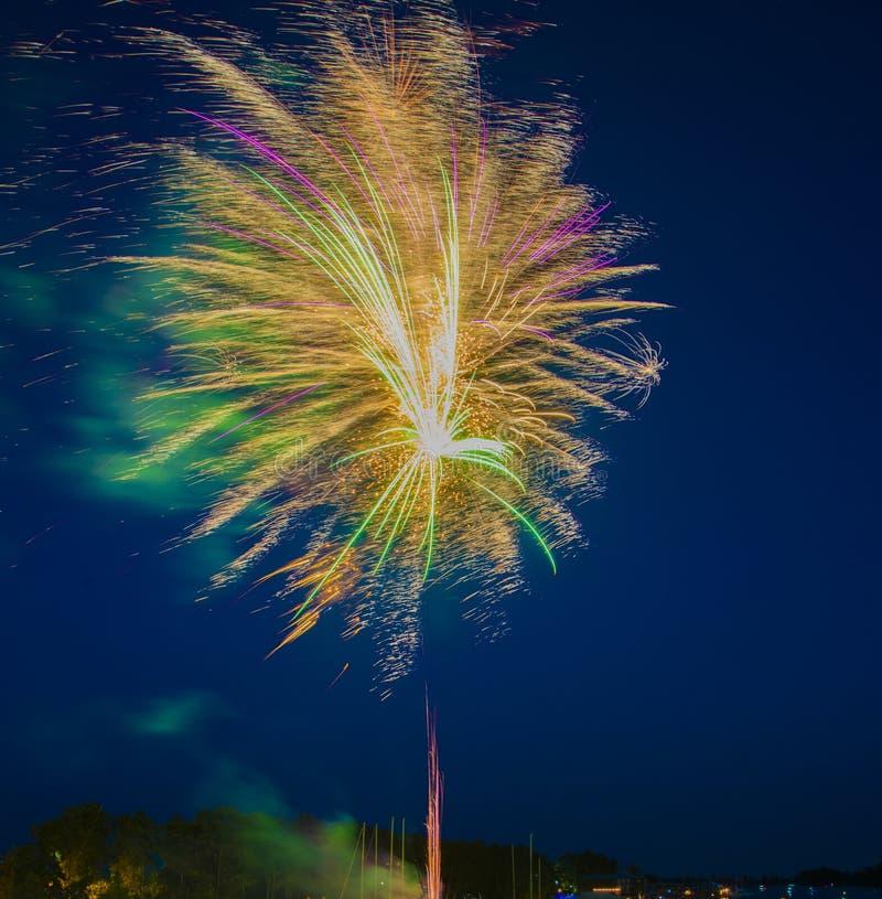 Fuegos artificiales en una noche ventosa sobre el agua imagenes de archivo