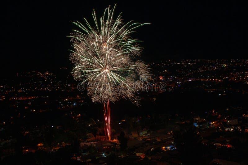 Fuegos artificiales grandes sobre una ciudad por noche imagenes de archivo