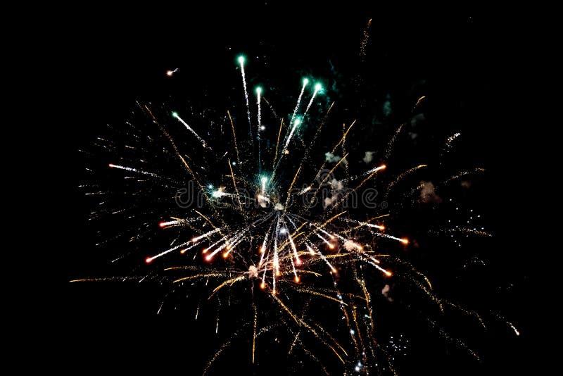 Fuegos artificiales pirotécnicas blancos y anaranjados en la noche imágenes de archivo libres de regalías