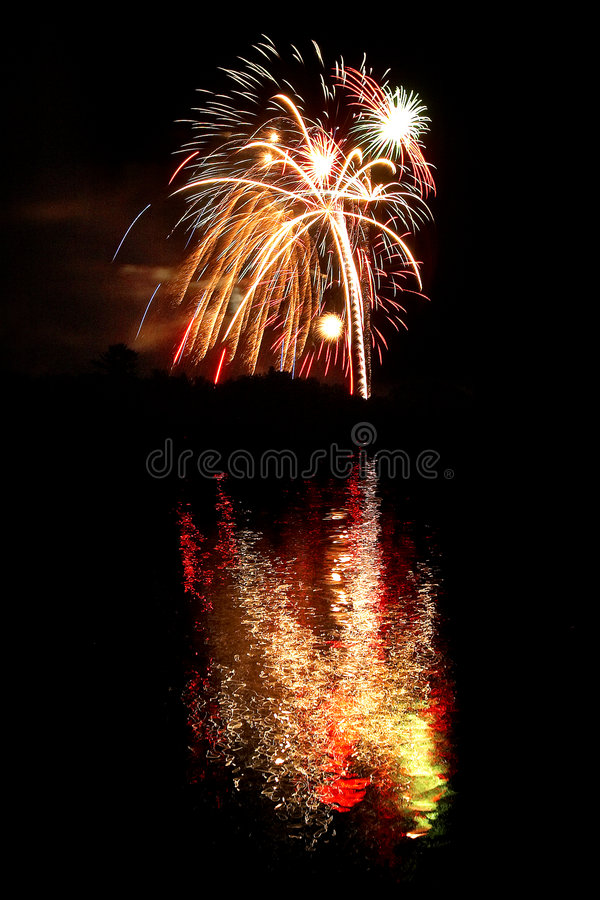 Fuegos artificiales reflejados en un lago imagenes de archivo