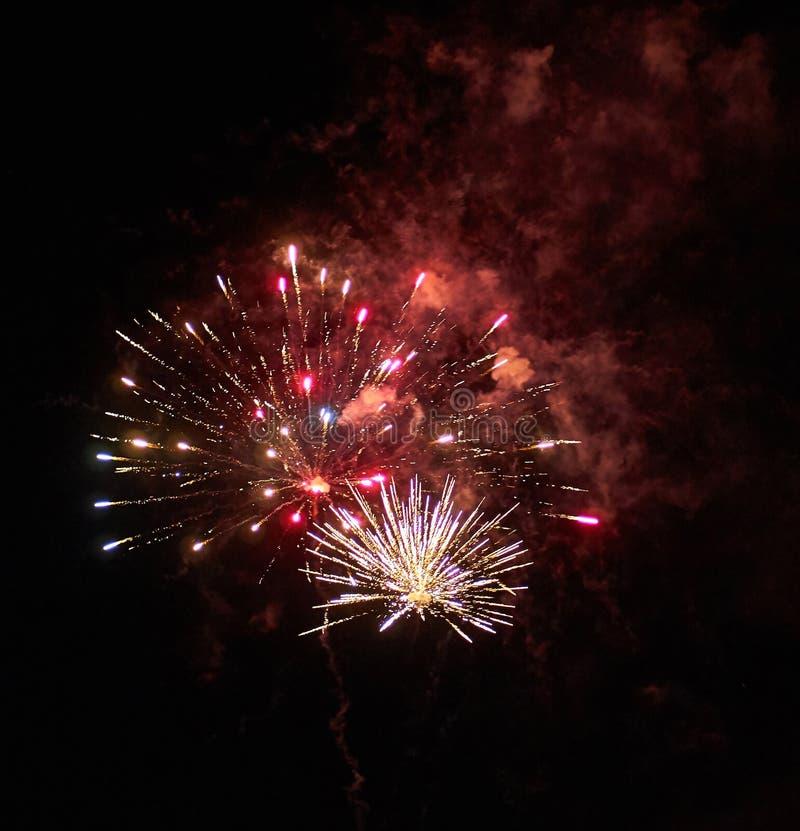 Fuegos artificiales y humo rojos brillantes coloridos en el fondo del cielo nocturno fotografía de archivo