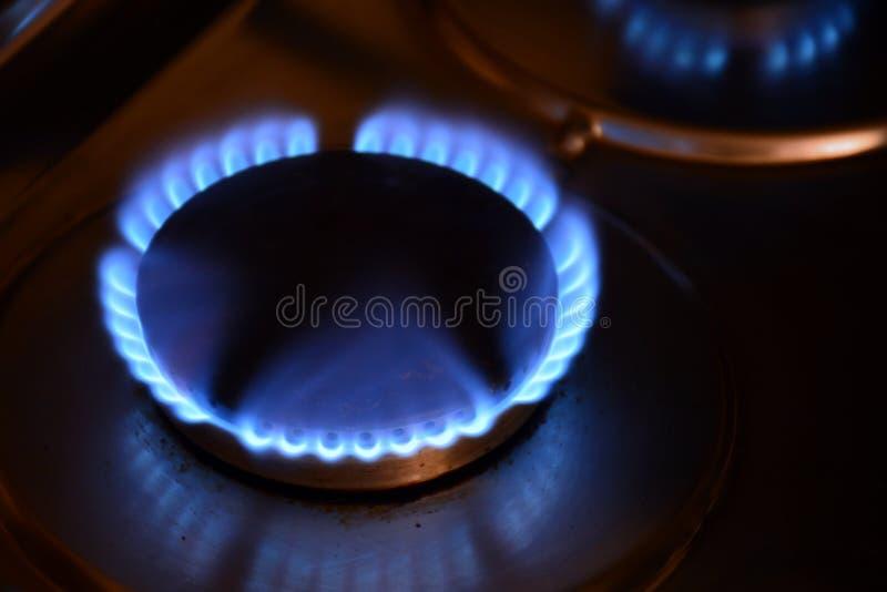 Fuegos encendidos de una hornilla de gas. Several burners lit in the dark with flame of a butane gas burner royalty free stock photos