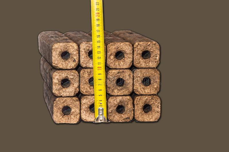 Fuel briquettes folded in rows on a white background. Wooden  briquettes are an environmentally friendly fuel source that are used to start a fire. They are stock images