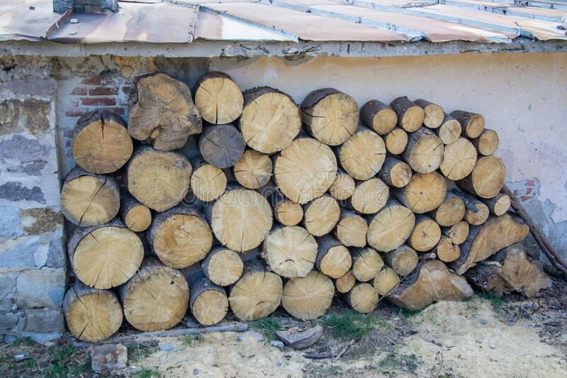 Pile of big round woods in front of a house. Logs, Fuel for heating. Wooden firewood stacked. Natural wood background. Fuel for heating during the winter royalty free stock photos
