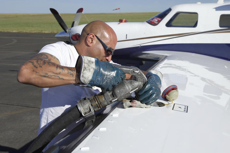 Fuel nozzle filling up aircraft. BITBURG, GERMANY - 29 MAY 2011: efueling private piston planes on the airport runway. Muscular man holding tank gun in his hand royalty free stock image
