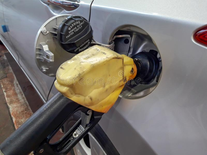 Fuel nozzles adding gasoline fuel in car at a pump gas station. stock photography