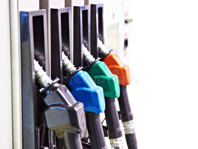 Fuel nozzles isolated. Fuel nozzles on filling station isolated white stock images