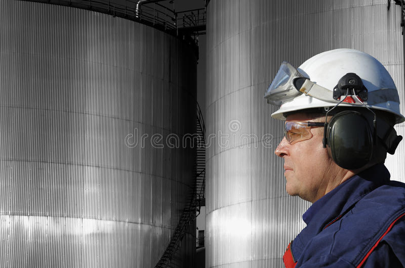 Fuel tanks and oil-worker. Oil-worker in profile with large fuel storage tanks in background royalty free stock photos