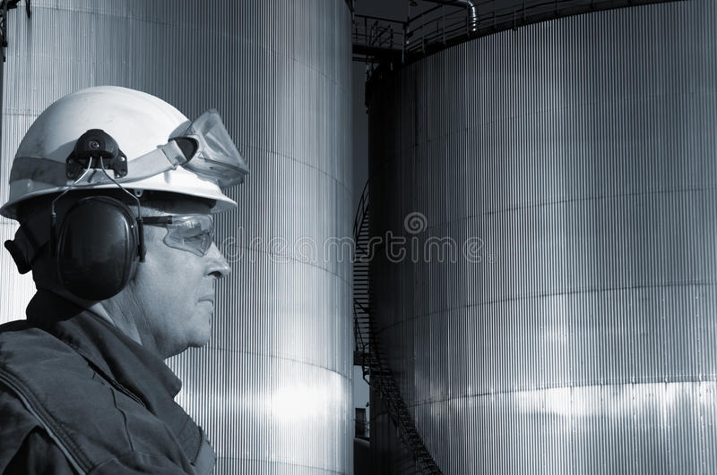 Fuel tanks and oil worker. Oil-worker, engineer in front of large fuel-storage tanks, blue toning concept stock photos