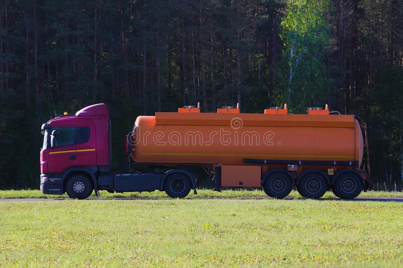 Fuel truck is driving along a road in the forest stock photography
