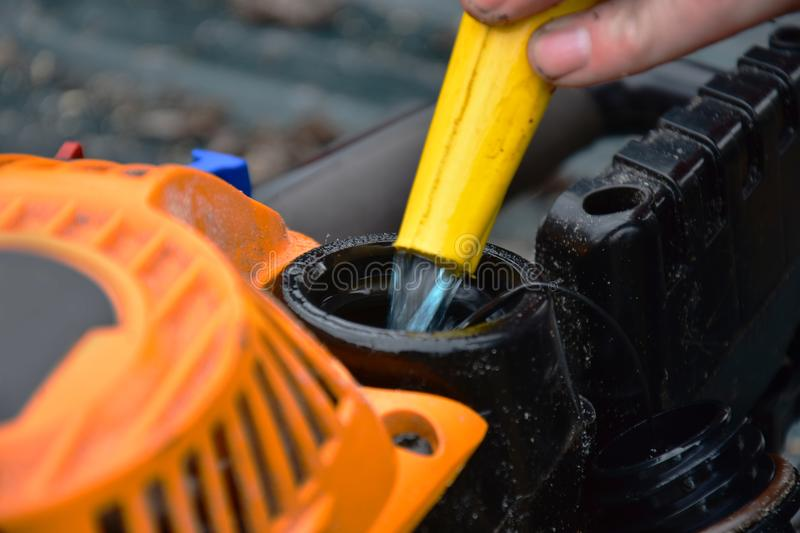 Fueling a Chainsaw. A close up image of gas being added to a dirty old chainsaw stock photo