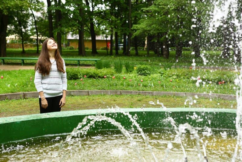 Fuente bastante adolescente del reloj de la muchacha en el parque fotografía de archivo