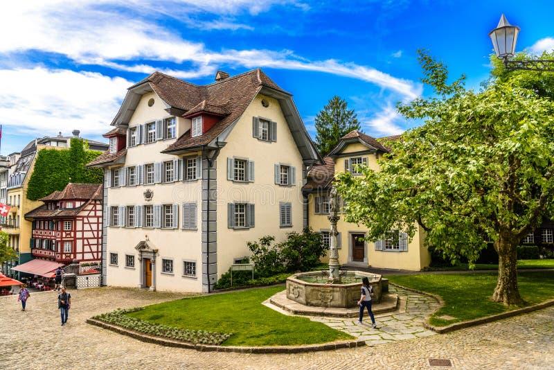 Fuente cerca de la casa y del árbol, Alfalfa, Lucerna, Suiza fotografía de archivo