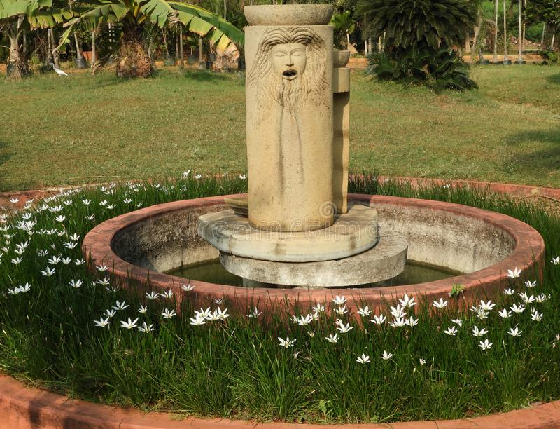 Fuente con las flores alrededor con la boca del rostro humano abierta imagen de archivo