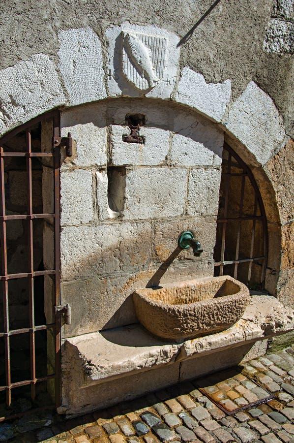 Fuente de agua de piedra vieja con las puertas del hierro y el escudo heráldico en el arco en Annecy imagen de archivo libre de regalías