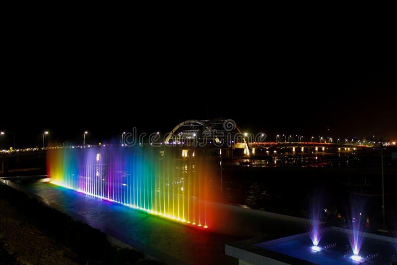 Fuente de agua del arco iris y birdge en la noche fotos de archivo