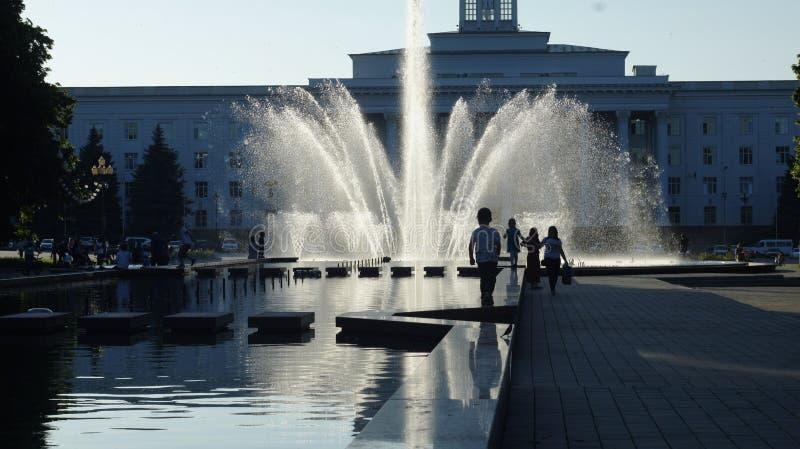 Fuente de la ciudad en la puesta del sol o fotos de archivo