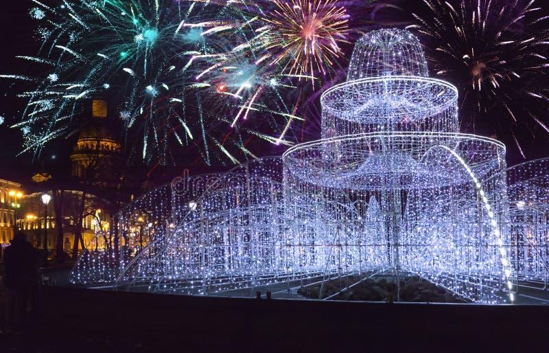 Fuente de los fuegos brillantes en el cuadrado delante de St Isaac Cathedral en los fuegos artificiales de Nochevieja y de la Nav fotos de archivo