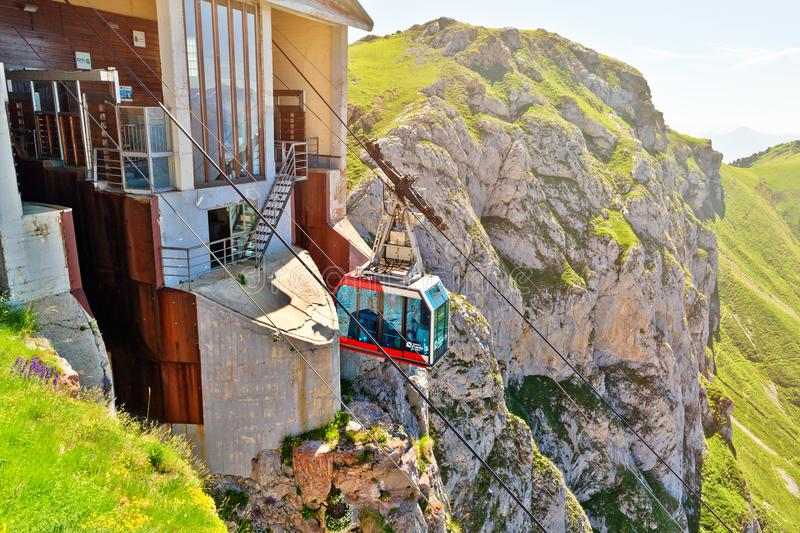 FUENTE DE,SPAIN - JULY 10, 2016: The cabin of the ropeway Teleferico Fuente De. The cabin arrives to the station at mountain top in beams of the sunset sun stock images