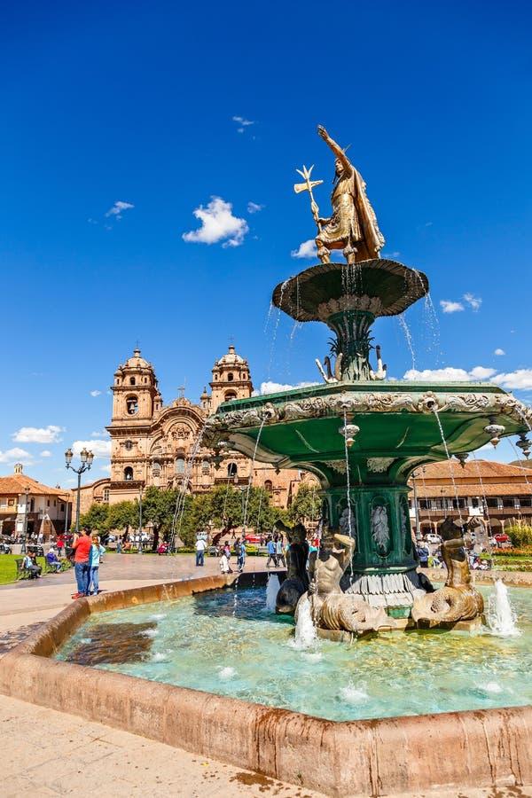 Fuente del emperador Incan Pachacuti e iglesia de la sociedad de Jesús en Plaza De Armas, Cuzco, Perú foto de archivo libre de regalías