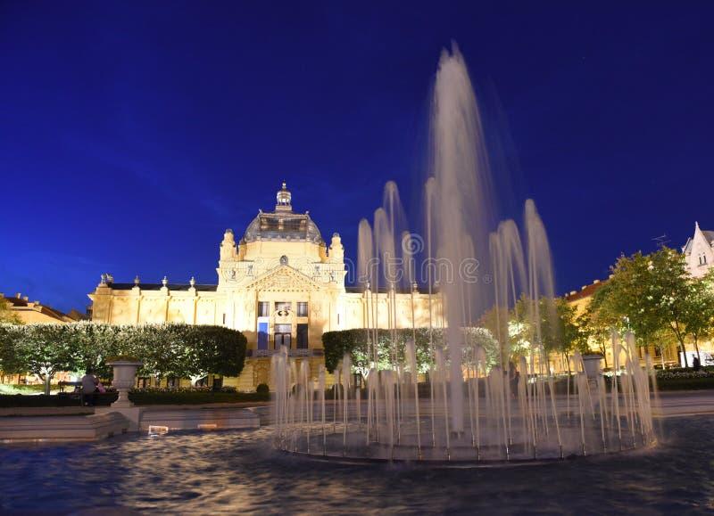 Fuente en el parque de Ledeni y el pabellón del arte en la noche en Zagreb, CRO (coordinadora) fotos de archivo libres de regalías
