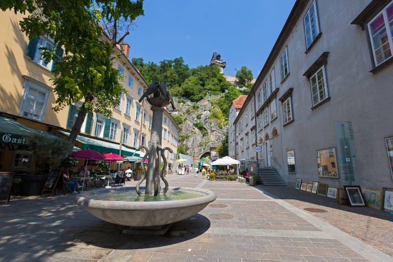 Fuente en Schlossbergplatz con el fondo de la escalera a la colina del castillo de Schlossberg en Graz, Austria imagenes de archivo