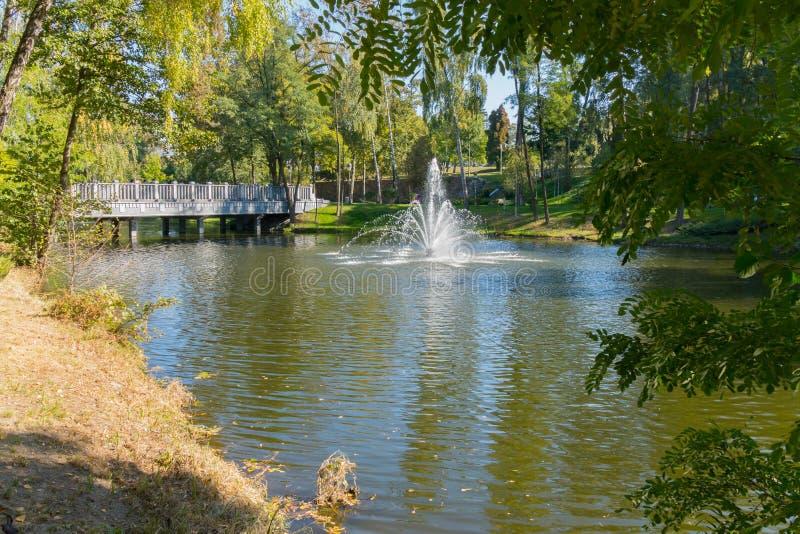 Fuente espaciosa sobre el río cerca del puente en el parque con las plantaciones del árbol imágenes de archivo libres de regalías