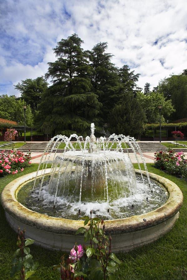 Fuente redonda encantadora en un jardín de rosas foto de archivo libre de regalías