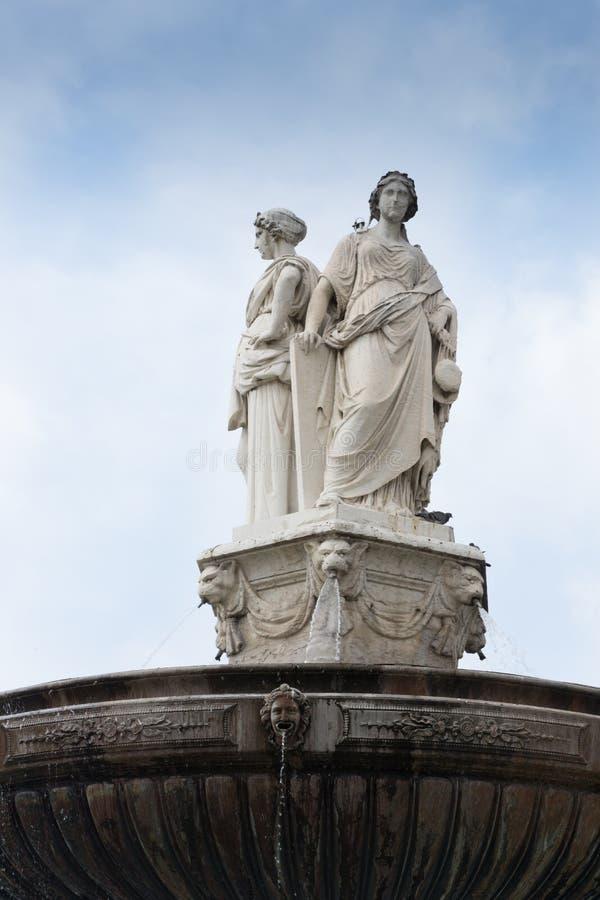 Fuente rematada con las estatuas talladas de dos mujeres imagen de archivo