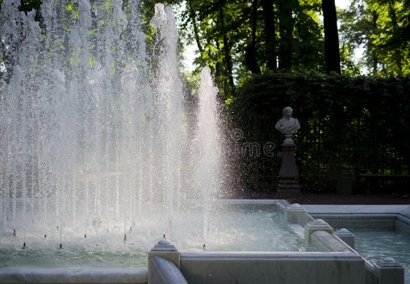 Fuente y estatua en el parque imagenes de archivo