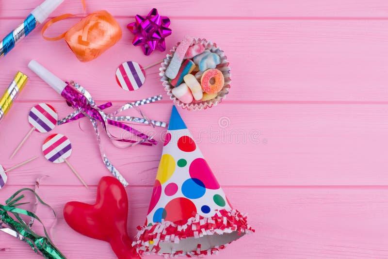 Fuentes coloridas de la fiesta de cumpleaños en la madera rosada fotografía de archivo