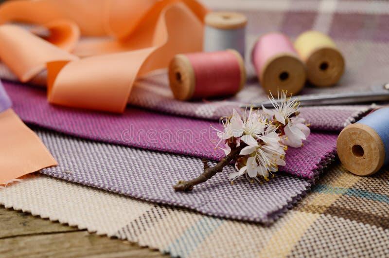 Fuentes de costura, agujas, tijeras en el fondo colorido de la materia textil del yute imagen de archivo libre de regalías