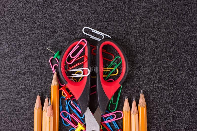 Fuentes de escuela, accesorios de los efectos de escritorio en fondo negro foto de archivo libre de regalías
