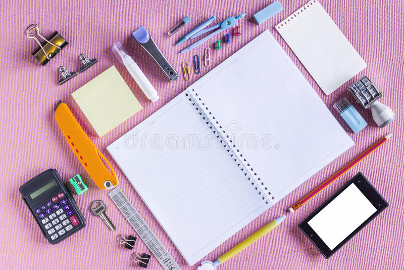 Fuentes de escuela coloridas organizadas por el tipo alrededor del cuaderno abierto a la página en blanco dispuesta imagen de archivo libre de regalías